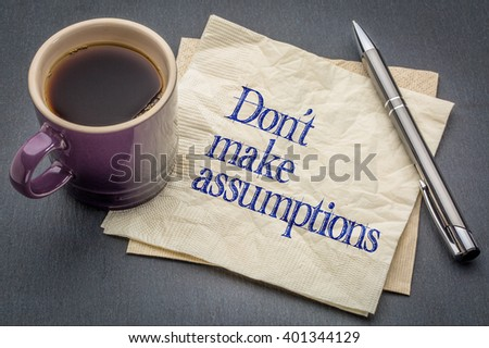 Don not make assumption advice or reminder - handwriting on a napkin with cup of coffee against gray slate stone background - stock photo
