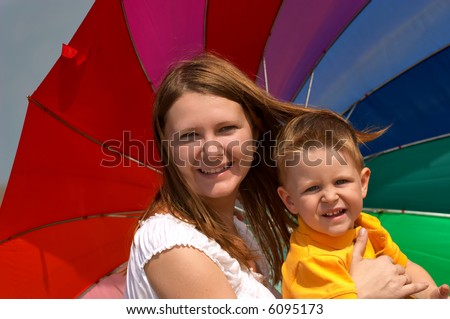 Don't depend on weather conditions. Happy young woman and kid under brightly colored umbrella having fun outdoors.