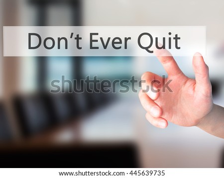 Don't Ever Quit - Hand pressing a button on blurred background concept . Business, technology, internet concept. Stock Photo - stock photo