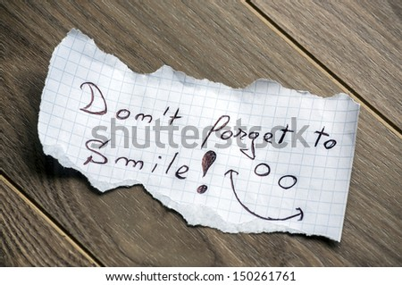 Don't forget to Smile - Hand writing text on a piece of paper on wood background - stock photo