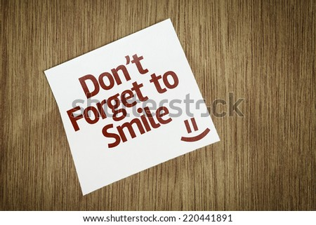 Don't Forget to Smile on Paper Note on texture background - stock photo