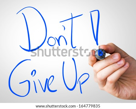 Don't Give Up hand writing with a blue mark on a transparent board - stock photo