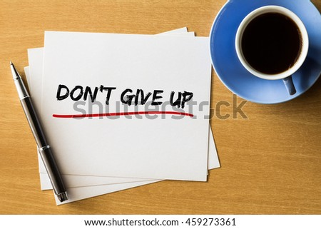 Don't give up - handwriting on papers with cup of coffee and pen, motivation concept