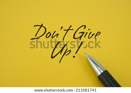 Don't Give Up! note with pen on yellow background