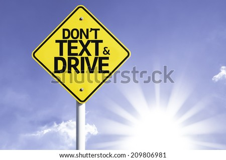 Don't text and Drive road sign with sun background - stock photo