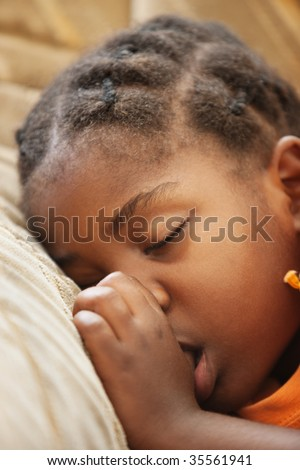 don't worry be happy, African child with braids sleeping on the couch - stock photo