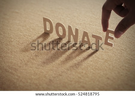 DONATE word on compressed board with human's finger at E letter