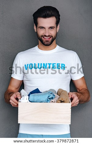 Donating with pleasure. Confident young man in volunteer t-shirt holding donation box in his hands and looking at camera with smile while standing against grey background