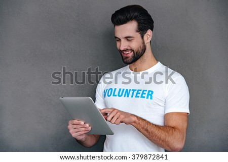 Donation by one click. Confident young man in volunteer t-shirt using his digital tablet with smile while standing against grey background