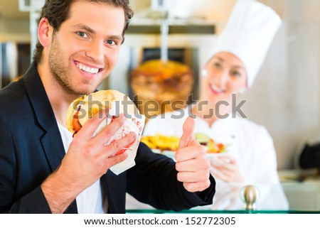 Doner kebab - friendly vendor and customer in a Turkish fast food eatery, with a freshly made pita bread or kebab in front of skewer - stock photo
