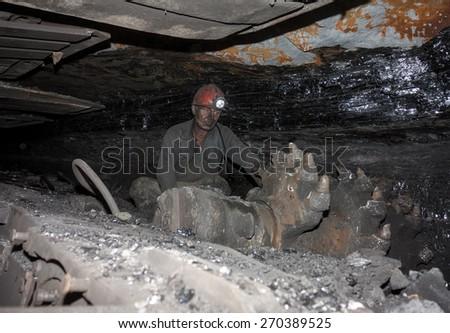 Donetsk, Ukraine - August, 16, 2013: Miner near a coal mining shearer. Mine is named Chelyuskintsev - stock photo