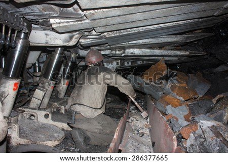 Donetsk, Ukraine - August, 16, 2013: Miner working in a confined space clears from the slag conveyor. Mine is named Chelyuskintsev - stock photo
