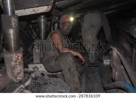 Donetsk, Ukraine - August, 16, 2013: Miners at work in cramped conditions underground excavation. Mine name Chelyuskintsev - stock photo
