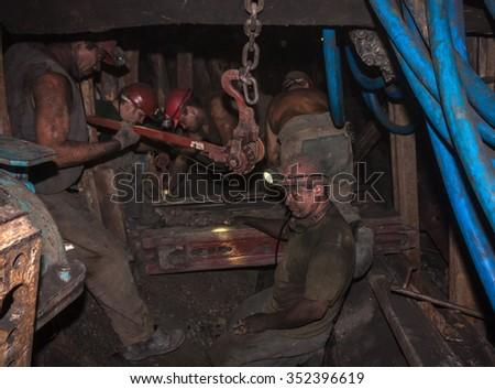 Donetsk, Ukraine - August 16, 2013: Miners at work in cramped conditions underground excavation. Mine name Chelyuskintsev - stock photo