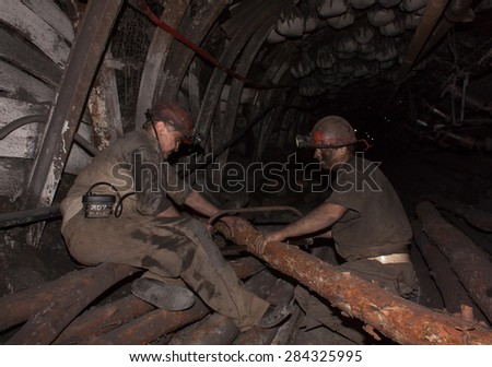 Donetsk, Ukraine - August, 16, 2013: Miners sawn timber for the construction of roof support in underground mines. Mine name Chelyuskintsev - stock photo