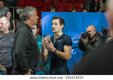 DONETSK, UKRAINE - FEB. 15: Renaud Lavillenie - The Olympic champion 2012 talking with the coach after the record jump on Samsung Pole Vault Stars meeting on February 15, 2014 in Donetsk, Ukraine. - stock photo