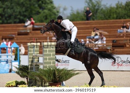 "DONETSK, UKRAINE - JUNE 07, 2009: Unknown rider overcomes the obstacle at the racehorse in the jumping competition ""Donbass Tour 2009"" CSN** 2 stage on June 07, 2009 in Donetsk, Ukraine."