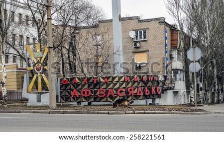 "DONETSK, UKRAINE - March 4, 2015: Dog wanders near a sign that says ""Zasyadko mine"", following an explosion in the separatist-held eastern Ukrainian area of Donetsk.  - stock photo"