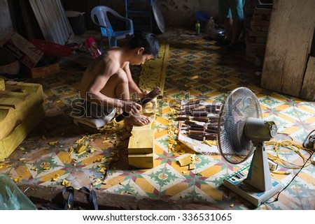 Dong Anh, Hanoi, Vietnam - Sep 20, 2015: Asian male worker makes wood carving in very small and narrow workshop in Dao Thuc village. Earning of carving workers is low in Vietnam