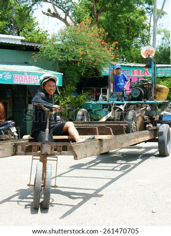 DONG THAP, VIET NAM- JULY 25: Asian man control motorized vehicle moving on route, he long, unsafe vehicle renovate as home made, this circulate on street make danger for people, Vietnam, Feb 25, 2014