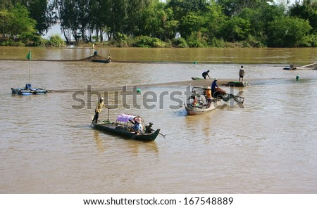 DONG THAP, VIET NAM- NOV 12: Group of fisherman catching fish by net on river, they row the boat along the river and spread a net to catch fish in Dong Thap, Viet Nam on Nov 12, 2013