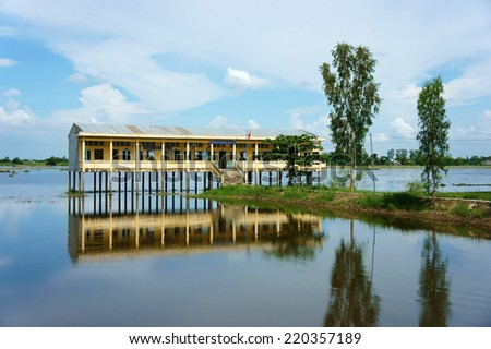 DONG THAP, VIET NAM- SEPT 19: Landscape of Vietnamese shool in flooded season, shool reflect on water, group of row boat floating on river, vehicle of waterway Mekong Delta, Vietnam, Sept 19, 2014