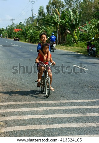 DONG THAP, VIET NAM- SEPT 23, 2014: Two unidentified Asian kid ride bicycle on country road in danger situation, Vietnamese children cycling very dangerous at Mekong Delta, Vietnam