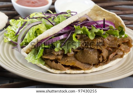 Donner Kebab - Turkish donner meat in a pitta bread served with chilli sauce, garlic mayonnaise and crunchy salad. - stock photo