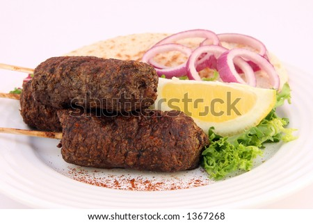 Donner Kofte kebabs on skewers on white plate with lettuce, onion and lemon, copy space. - stock photo