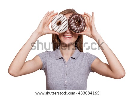 Donut eyes. Attractive young woman holding donuts like eyewear over white background.. - stock photo