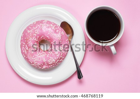 Donut with cup of hot coffee, top view. Photo in a pink color scheme