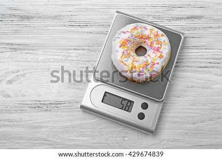 Donut with digital kitchen scales on wooden background - stock photo