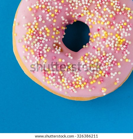 donut with sprinkles on turquoisebackground - stock photo