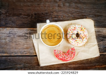 Donuts and coffee on a dark wood background. toning. selective focus on red donut - stock photo