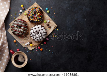 Donuts and coffee on stone table. Top view with copy space - stock photo