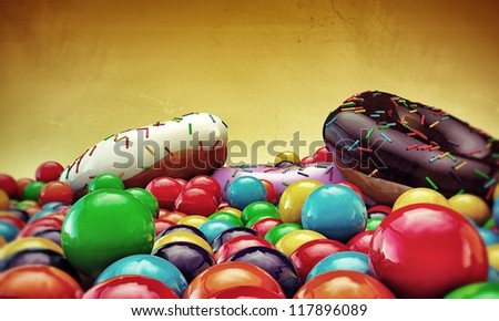 donuts and gumballs isolated on yellow background - stock photo