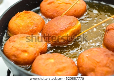 Donuts frying in deep fat. Preparation of traditional donuts