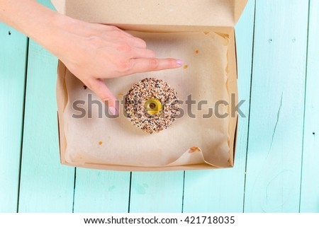 Donuts in box on wooden table. Top view - stock photo