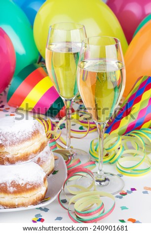 Donuts, Sparkling wine, streamers, confetti and party hat/party/carnival - stock photo