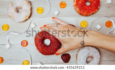 Donuts, sweetmeats candy and strawberry on wooden background. Flat lay background of homemade glazed and filled donuts and woman hand. Assorted colorful red, white sweet sugar donuts and sweets. - stock photo