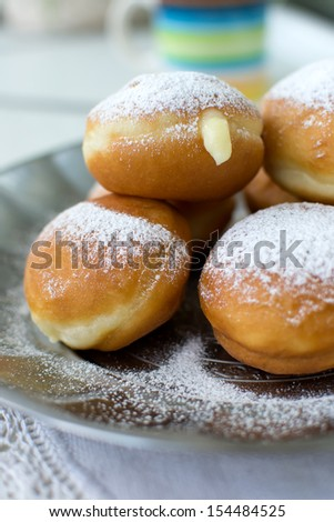 Donuts with cream, sprinkled with powdered sugar - stock photo