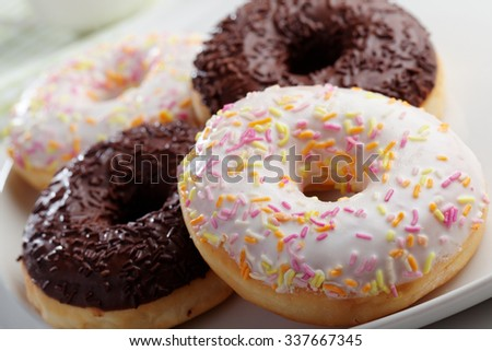 Donuts with frosting and sprinkles on a plate - stock photo