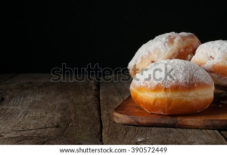 Donuts with powdered sugar on wooden table on black background close-up with space for your text - stock photo