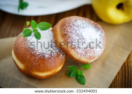 donuts with quince filling sprinkled with powdered sugar - stock photo