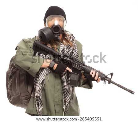 DOOMSDAY PREPPER | Environmental disaster. Post apocalyptic female survivor wearing a gas mask and rifle looking at camera with her go bag. - stock photo