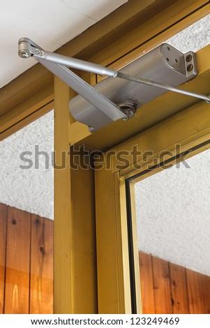 Door closer keeps a glass door close. - stock photo