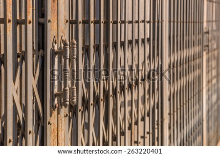 Door handle on old iron gate background. - stock photo