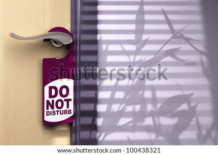 Door handler where its written do not disturb hanged onto a handle color tone is purple there is a wooden door on the left side and room for text at the right side - stock photo