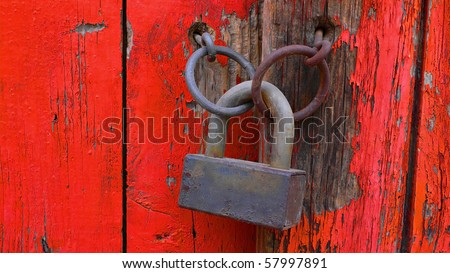Door handles on old red wooden door with a rusty old padlock