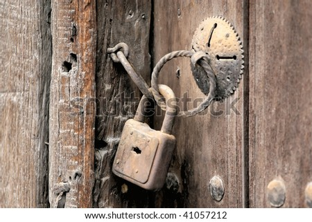 Door handles on old wooden door with a rusty old padlock